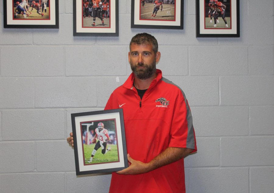 Head football coach Alan Peacock holds a framed photo of Dan Ellington, a 2016 CHHS graduate who played quarterback for the Mustangs. Ellington is now quarterback for Georgia State University.