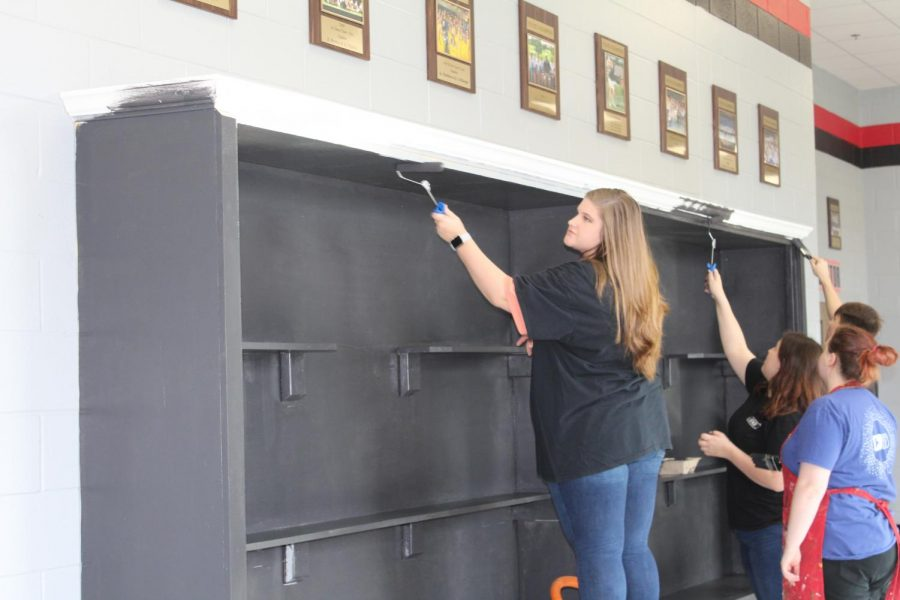 Hailey Ellis and other students in Whitney Lantrips Gifted Art classes paint the schools new trophy cases.