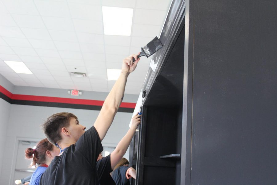 Keegan Hendrix helps paint the new trophy cases installed in the gym hall. The trophy cases are a gift from the Class of 2018 and were built by Assistant Principal Zack Sims.