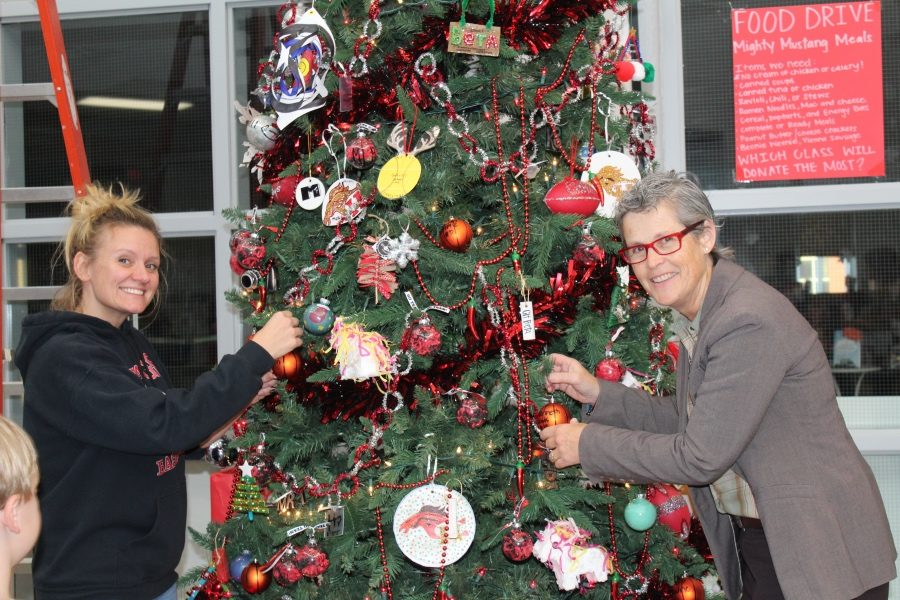 Student Council co-sponsor Meredith Smith, left, and Assistant Principal Brenda Case help decorate the CHHS Christmas tree during Deck The Hill.