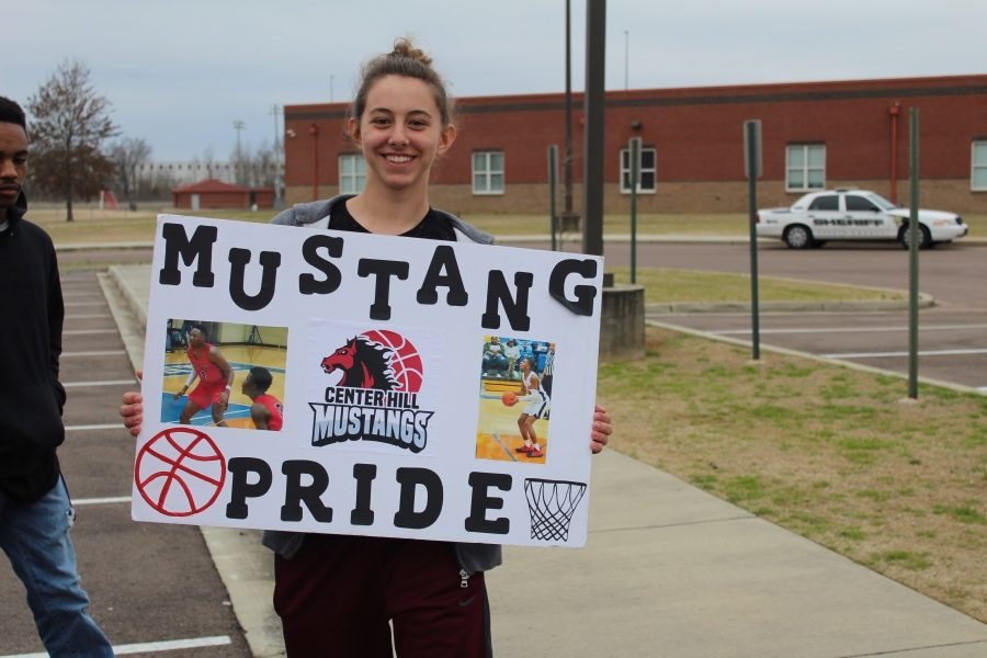 Kierstyn Bell, sophomore, holds a Mustang Pride sign to show her support for the boys basketball team.