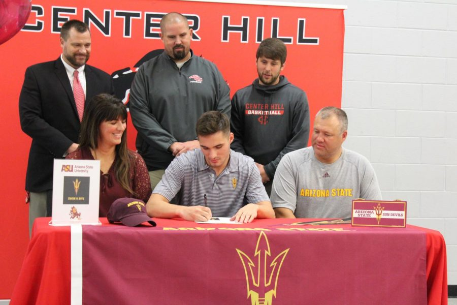 With+his+parents%2C+coach+and+school+administrators+looking+on%2C+Taylor+Williams+officially+signed+today+to+swim+for+Arizona+State+University.+Williams+is+the+first+swimmer+from+Center+Hill+High+School+to+go+to+a+D1+program.