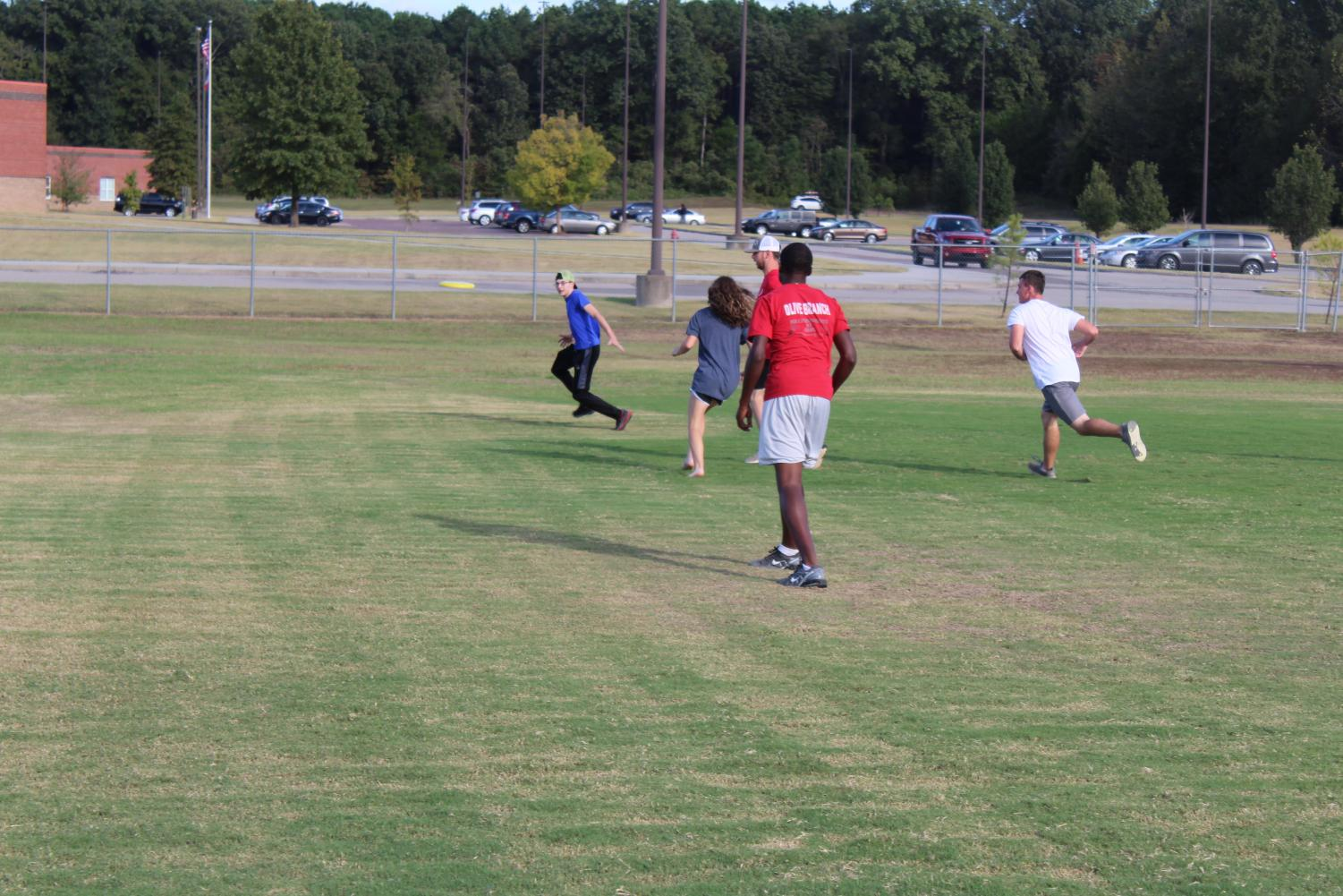 "Trey Stuard, far left, runs to catch a flying disc at Ultimate practice. Stuard, senior captain of the Ultimate team, has played all four years of high school and described the non-contact sport as ""kind of like football."""