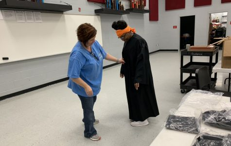 Cathy Dawson helps Shamyra Thomas try on her cap and gown June 2. Thomas said with a family of 10, the limit of six people at her graduation ceremony