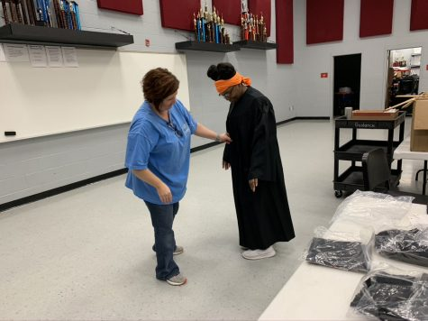 "Cathy Dawson helps Shamyra Thomas try on her cap and gown June 2. Thomas said with a family of 10, the limit of six people at her graduation ceremony ""is going to be hard."""