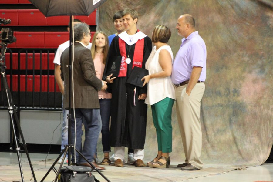 Surrounded by his family, Dru Hines prepares to have graduation pictures taken by a Holland Studio photographer. Hines graduated with special distinction June 9 in a ceremony that followed CDC guidelines.