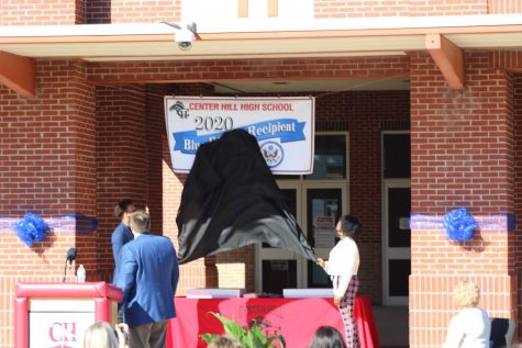 Principal Doug Payne looks on as seniors Zandon Haralson, left, and Candice Buford unveil the National Blue Ribbon banner at the school