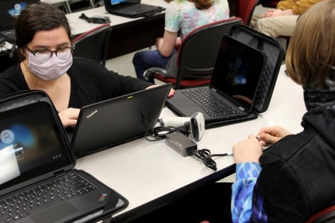 Distance Learning Team member Madeline Dormois helps set up a student laptop during one of the school's distribution days. DeSoto County Schools purchased devices for every K-12 student with money allocated by the Mississippi Legislature.