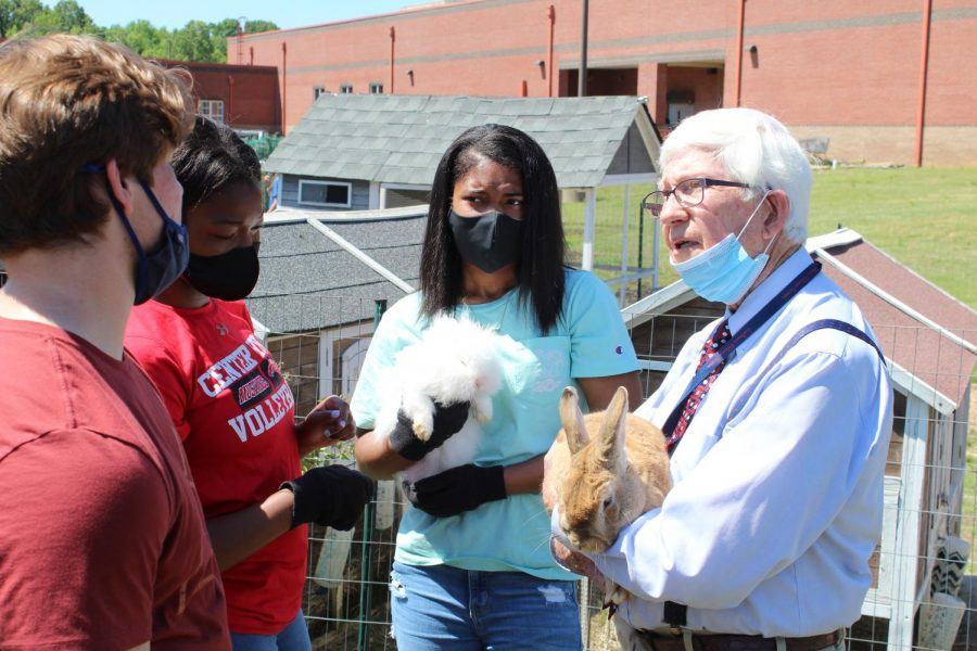 School Board member Milton Nichols, right, holds Cypress, a Flemish Giant rabbit, while talking to Resource Management students, from left, Barrett Dempsey, McKenzie Warner and Shainah Walker during a tour of the CHHS Farm May 6.