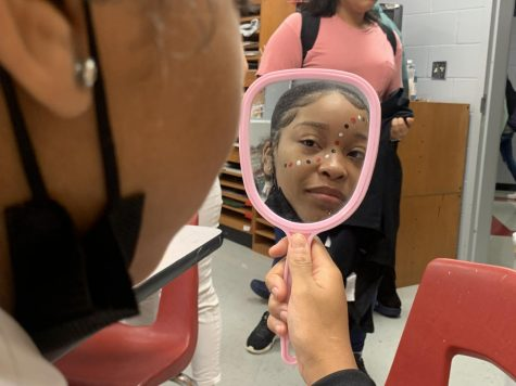 Jada Parker, sophomore, looks at her reflection after Art Society member Carrie Cardin, junior, painted her face with red, white and black dots for Game Day.